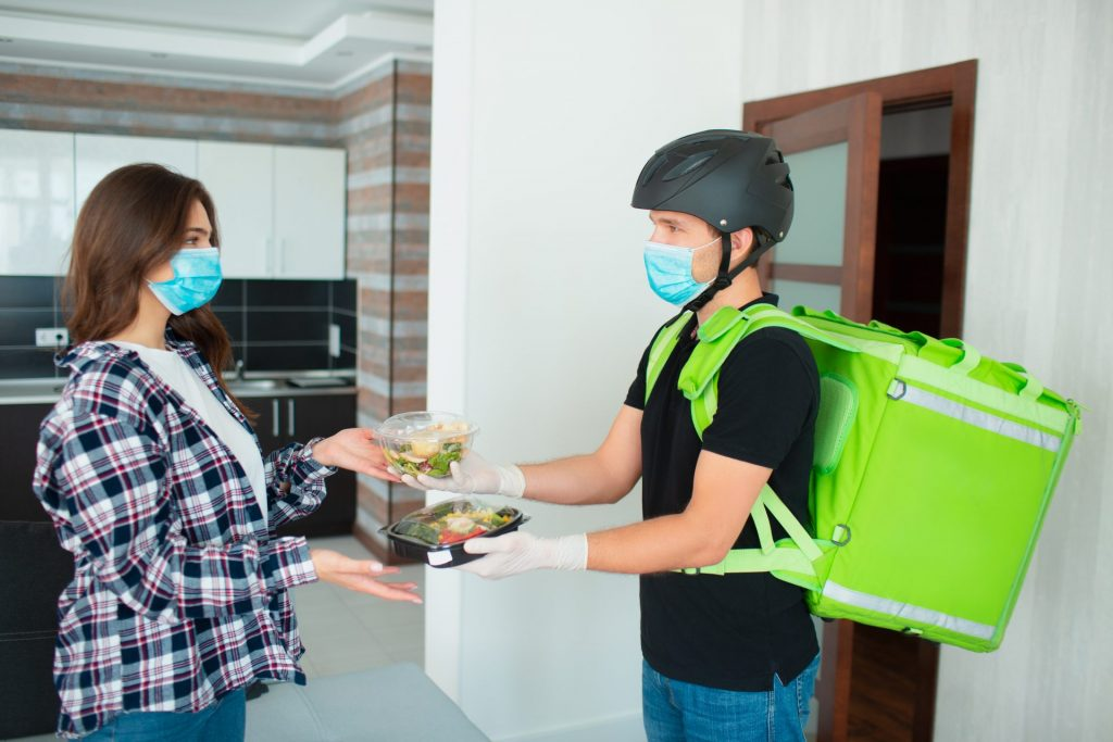 food-delivery-man-in-medical-mask-and-gloves-brought-salads-of-fruits-and-vegetables-in-plastic-boxes-to-the-young-woman-s-house